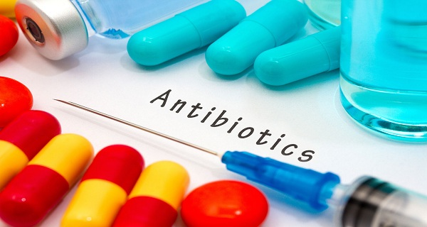 Antibiotics - Diagnosis Written On A White Piece Of Paper. Syringe And Vaccine With Drugs.